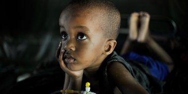 A child suffering from malaria recovers at a clinic in Mogadishu, Somalia. Photo credit: 2013_04_15_Clinic_D, AMISOM Public Information, CC0-1.0.